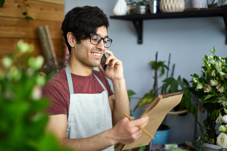 Young florist talking to client on smartphone